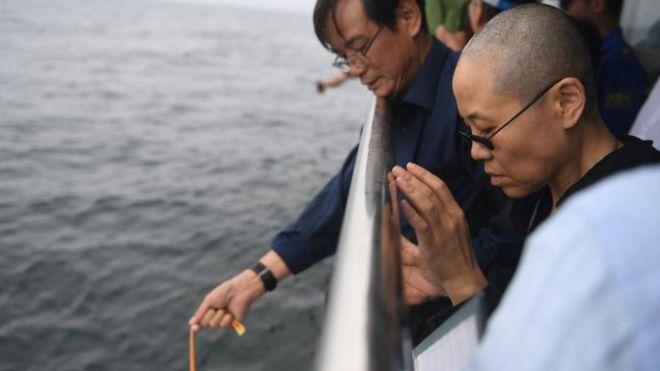 妻の劉霞さん(右)が祈るなか、劉暁波氏の遺骨は大連近くの海に散骨された