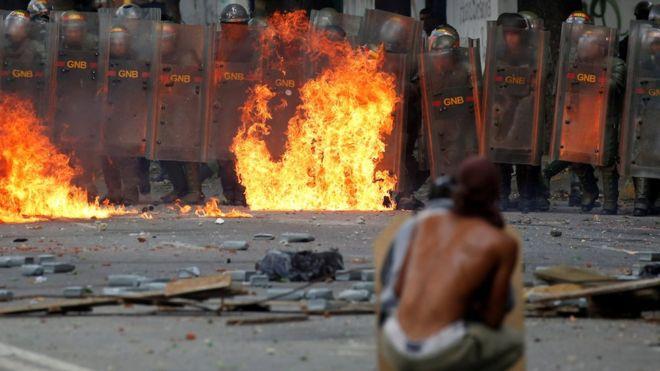 Hombre cubriéndose con un escudo casero contra funcionarios de la Guardia Nacional Bolivariana.