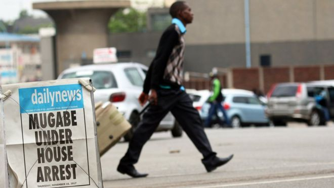 """A man crosses the road in Harare behind a local newspaper poster that reads """"Mugabe under house arrest""""."""