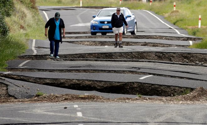 Local residents Chris and Viv Young look at damage caused by an earthquake, along State Highway One near the town of Ward, south of Blenheim on New Zealand's South Island, 14 November 2016