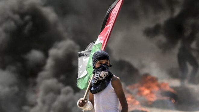 Menino carrega bandeira da Palestina