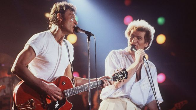 This file photo taken on April 2, 1985 shows French singers Eddy Mitchell (R) and Johnny Hallyday performing at the stadium in Bourges