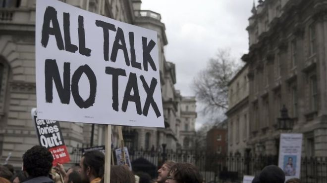 Demonstrators hold placards during a protest outside Downing Street in Whitehall, central London, 2016
