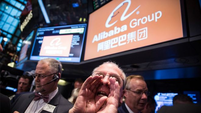 Alibaba sign appears behind a trader at the New York Stock Exchange