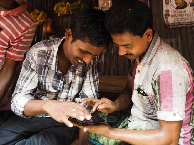 Bangladesh, 2014. Two men look at their phone