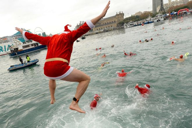 A participant in a Santa Claus costume jumps into the water during the 108th edition of the
