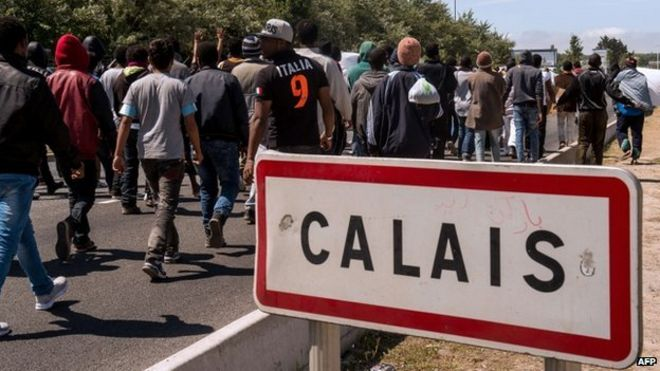 "Migrants walk past a ""Calais"" sign"