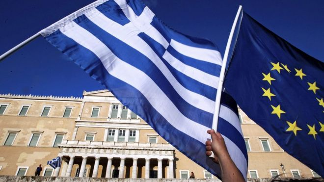 Protesters hold a Greek and a EU flag outside the parliament during a rally in Athens on 22 June 2015.