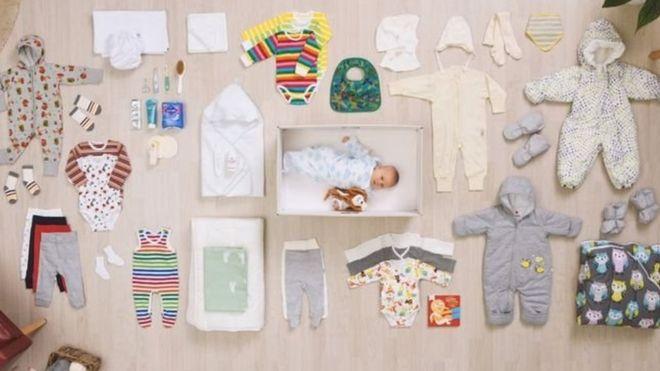 Bebé dentro de la caja de cartón junto a la ropa y otros objetos que son entregados a las madres en Finlandia (Foto: Kela)