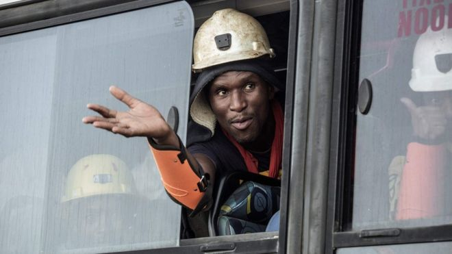 A rescued South African miner gestures out a bus window, 2 February 2018