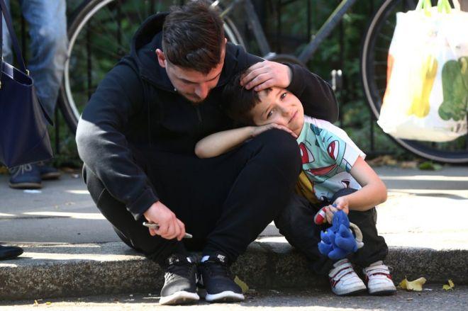 Un hombre sostiene la cabeza a un niño fuera de la Torre Grenfell, el edificio de viviendas incendiado en Londres.