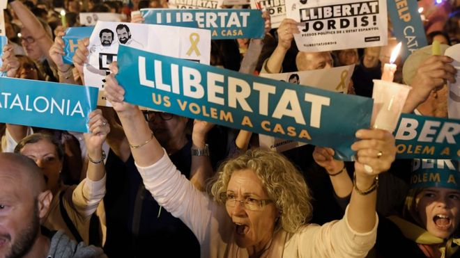 """People hold placards reading """"Freedom"""" during candle-lit demonstration in Barcelona against the arrest of two Catalan separatist leaders on October 17, 2017."""