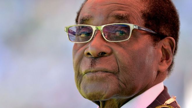 "This file photo taken on August 22, 2013 shows Zimbabwean President Robert Mugabe looking on during his inauguration and swearing-in ceremony at the 60,000-seater sports stadium in Harare. Zimbabwe""s former president Robert Mugabe was ousted by a ""military coup"" that forced his resignation, former cabinet minister Jonathan Moyo said in an interview with the BBC broadcast on January 11, 2018. Moyo, a former higher education minister under the last president and an ardent Mugabe loyalist, said Zimbabwe""s new President Emmerson Mnangagwa stole power and was leading an ""illegal regime""."