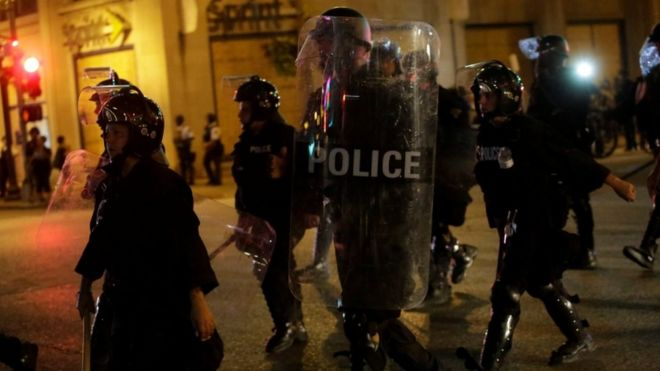 Police officers with riot gear march in St Louis street