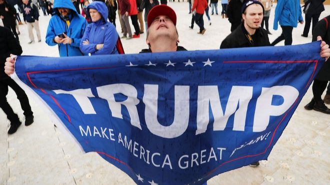 US President Donald Trump supporters react on the National Mall to the inauguration of US President Donald Trump on January 20, 2017 in Washington, DC