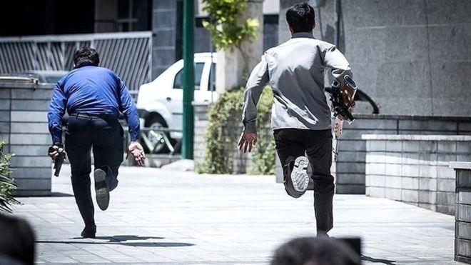Miembros de las fuerzas de seguridad iraníes corren durante el ataque al Parlamento en Teherán