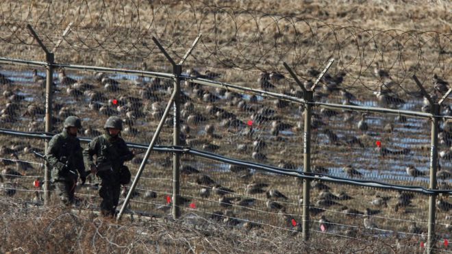 South Korean soldiers patrol a fence near the DMZ