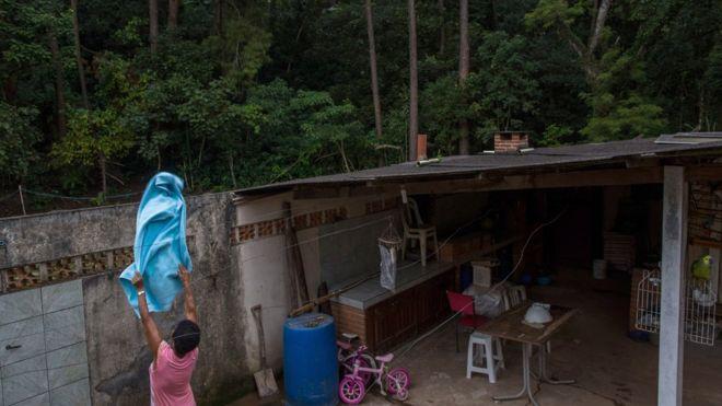 Mulher coloca roupa no varal em casa perto de mata