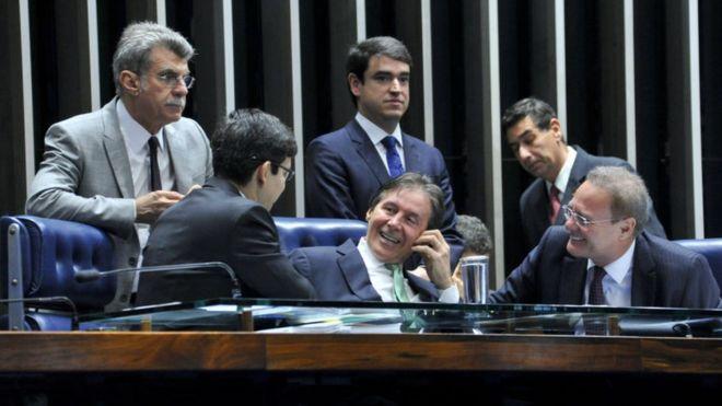 Senadores conversam e sorriem na mesa do plenário do Senado