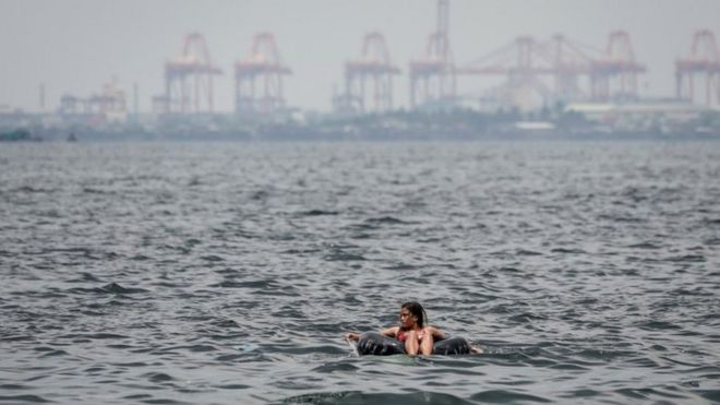 A woman floats on an inner tube of a rubber wheel on Easter Sunday at Manila Bay, Pasay City, south of Manila, Philippines, 01 April 2018
