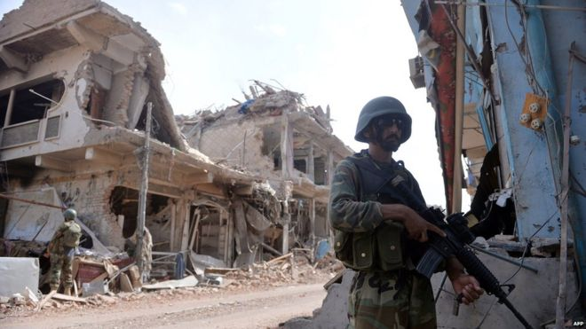 Pakistani soldiers stand guard at a destroyed empty bazaar during a military operation against Taliban militants in the main town of Miranshah in North Waziristan on 9 July 2014