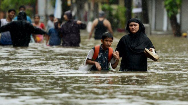 Una mujer camina con su hijo por una calle inundada en Mumbai.