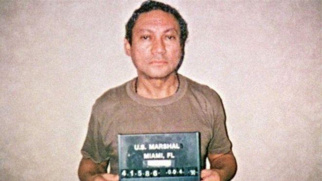 مانويل نورييغا يحمل لوحة أثناء التقاط صورة له في السجن