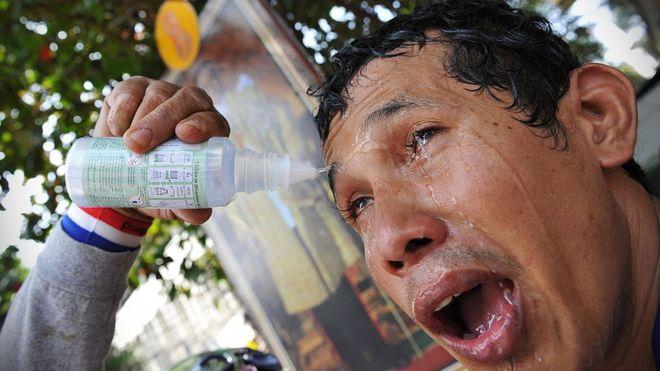 Un hombre trata de aliviar el efecto del gas lacrimógeno sobre sus ojos durante una manifestación antigubernamental en Bangkok, Tailandia, BANGKOK, en 2013.