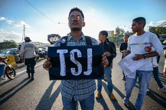 Joven con un cartel que dice TSJ protesta en Caracas, Venezuela.