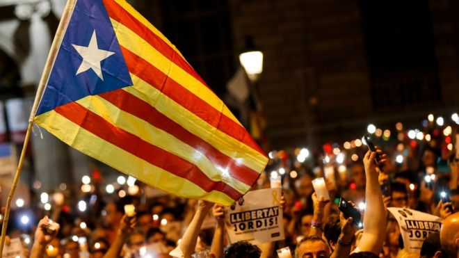 "People hold candles and a Catalan pro-independence ""Estelada"" flag during a demonstration in Barcelona against the arrest of two Catalan separatist leaders on October 17, 2017."