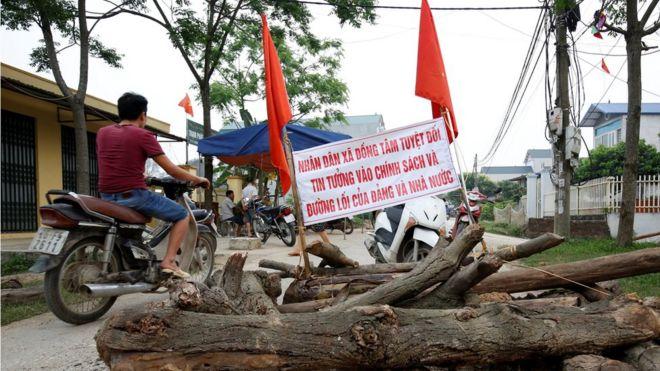 Người dân đi xe máy trên con đường có chướng ngại vật được dựng lên ở xã Đồng Tâm, huyện Mỹ Đức, Hà Nôi. Ảnh chụp ngày 20/4/2017