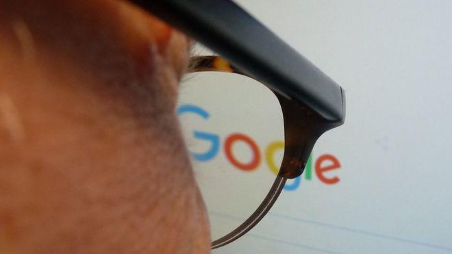 Hombre mirando la Página de Google En Una Pantalla.