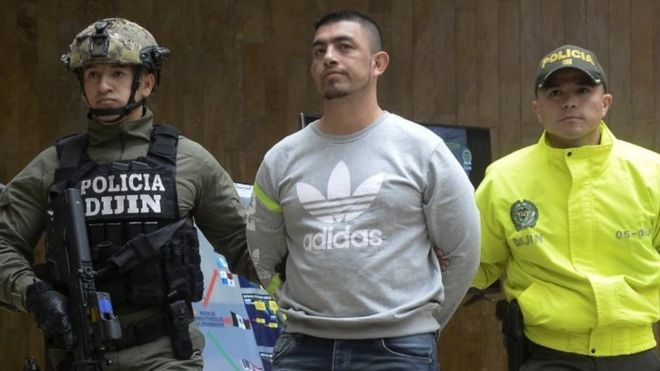 """In this file photo taken on April 11, 2017 Colombian Police officers escort Ecuadorean Washington Prado Alava aka """"Gerald"""" (C), during a press conference at the police headquarters in Bogota, Colombia."""
