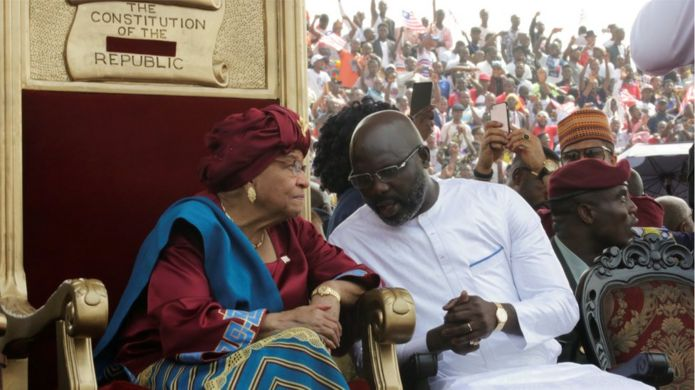 Liberia's former President Ellen Johnson Sirleaf and the new President elect George Weah speak during his swearing-in ceremony at the Samuel Kanyon Doe Sports Complex in Monrovia, Liberia, January 22, 2018