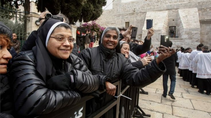 Nuns watch a procession at the Church of the Nativity in Bethlehem on December 24, 2017.