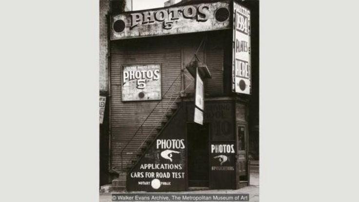 ایوانز عکسهای بسیاری از تابلوهای تبلیغاتی و علامتها گرفته، مانند استودیوی عکاسی گواهینامه، نیو یورک، ۱۹۳۴ (آرشیو واکر ایوانز، موزه متروپولیتن نیو یورک)