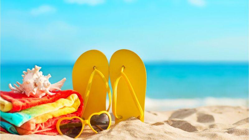 Un par de chancletas, una toalla y caracol en la playa.