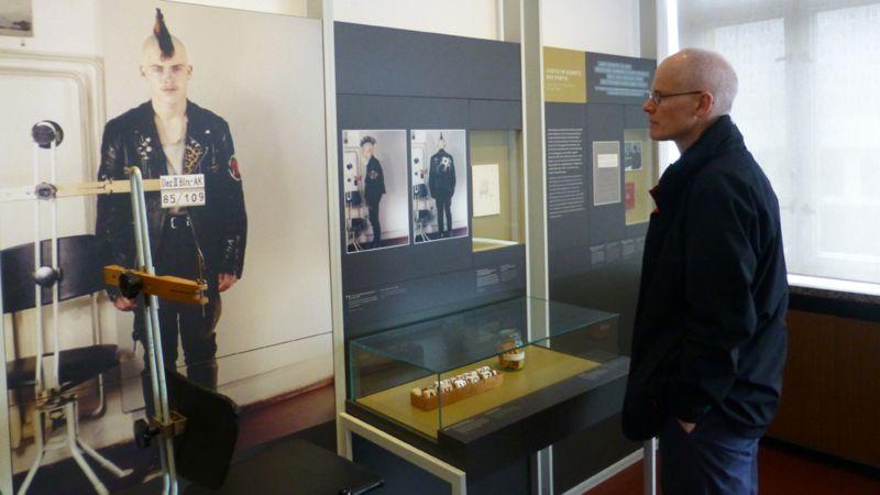 Chris Bowlby, Stasi Müzesi'ndeki bir punkın polis güreşlerine bakıyor