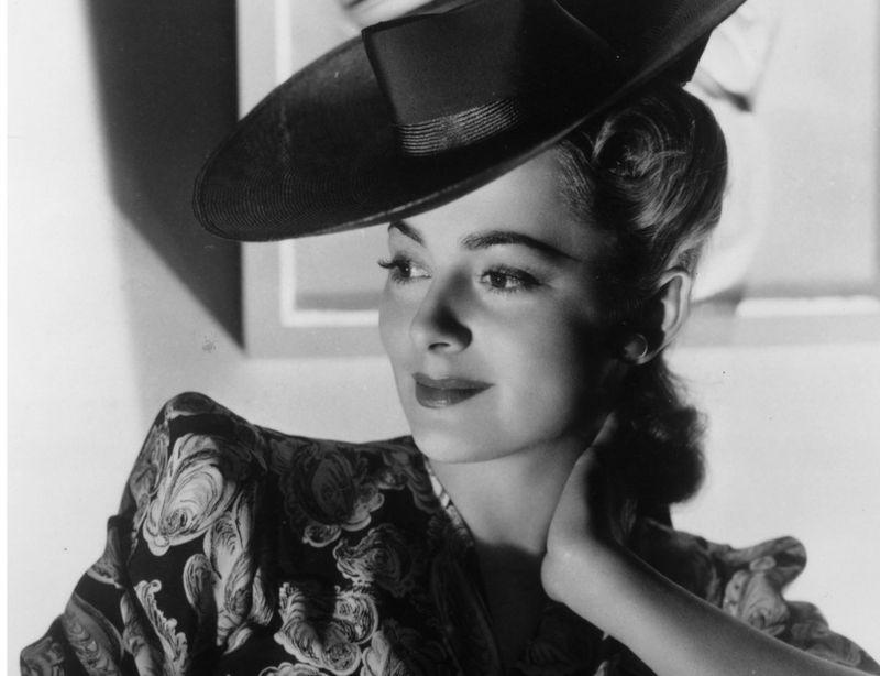 Olivia De Havilland'ın 1945 yılında çekilmiş fotoğrafıyla kabarık kollu ve koyu bir şapkalı bir elbisesinde dirseğine yaslanmış halde gülümseyerek