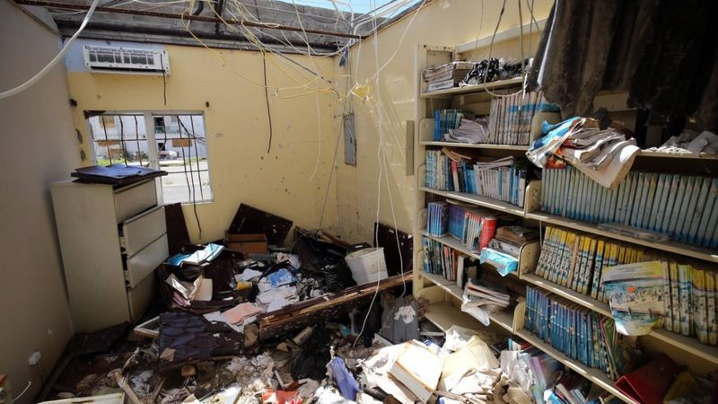 Una casa sin techo que exhibe una biblioteca. Hay libros y escombros en el piso.