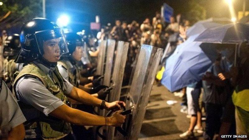 27 Eylül 2014'te Hong Kong hükümet kompleksini protestocılardan korumaya çalışan polis memurları