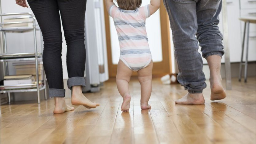 Mum and dad holding hands with walking baby
