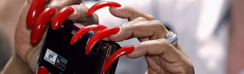 Woman with long fingernails holds a camera