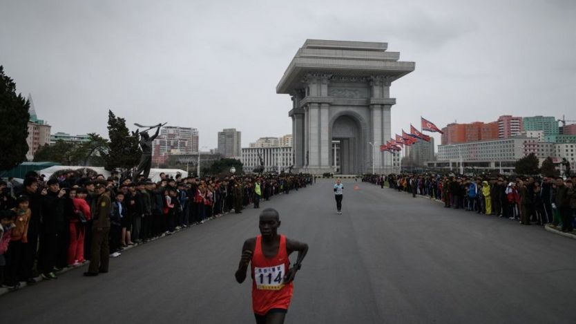 Competitors run past Pyongyang's Arch of Triumph near the end of the race