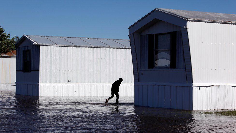 A young resident wades through flood waters at a trailer park after Hurricane Matthew hit Lumberton, North Carolina