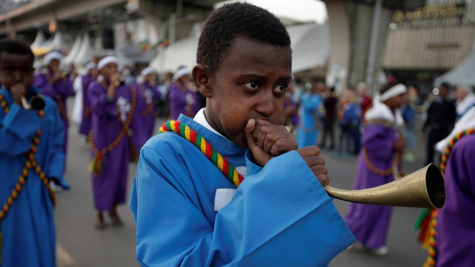 A choir member blows a traditional trumpet during the Meskel Festival
