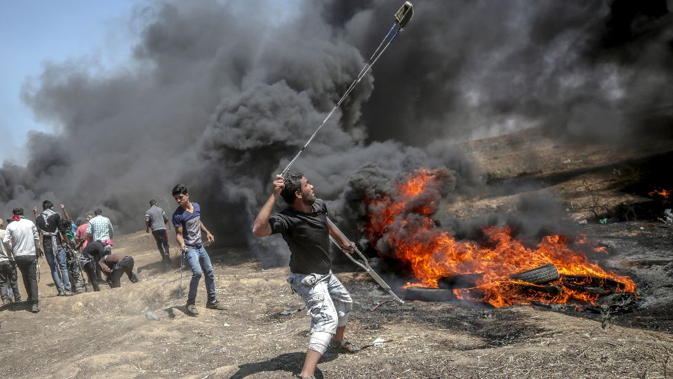 A Palestinian protester throws stones at Israeli troops during clashes after protests near the border with Israel in the east of Gaza Strip