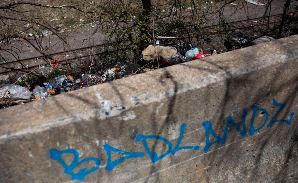 Márgenes de las vías del tren llenas de basura.