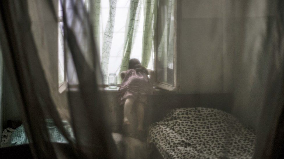 Marium Gabisonia, aged seven-years-old, looks out the second story window of the room she shares with her sister