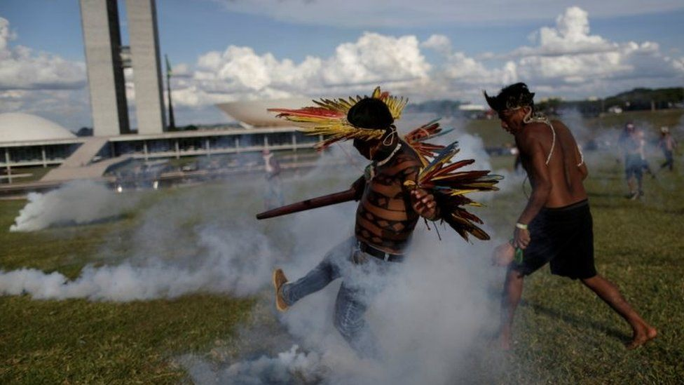 Indigenous protesters kick at canisters of tear gas at a demonstration in Brasilia on 25 April 2017